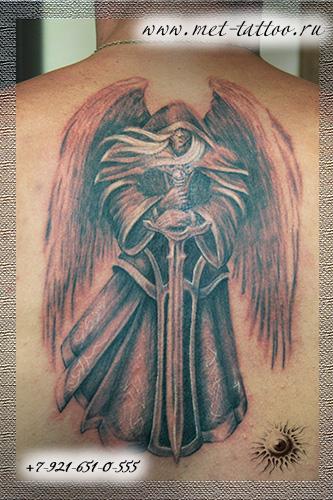 Тату ангел с мечом на спине между